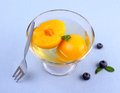 Peach compote in glass bowl with fork on blue background top view Stock Image