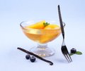 Peach compote in glass bowl with fork blueberries and vanilla close up Stock Photos