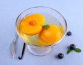 Peach compote in glass bowl with fork blueberries and vanilla top view Royalty Free Stock Images