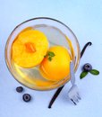 Peach compote in glass bowl with fork blueberries and vanilla top view Royalty Free Stock Photo