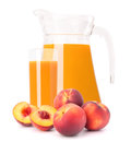 Peach fruit juice in glass jug isolated on white background cutout Royalty Free Stock Images