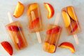 Peach iced tea popsicles with fruit slices on white marble Royalty Free Stock Photo