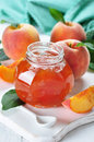 Peach jam in glass jar on white wooden background Royalty Free Stock Photography