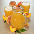Peach juice and fresh peaches on a brown table Stock Image