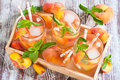 Peach lemonade homemade with ripe flat saturn shaped peaches and fresh mint Royalty Free Stock Image