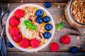 Peach smoothie bowl with raspberries, blueberries, granola and coconut Royalty Free Stock Photo