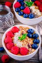 Peach smoothie bowls with raspberries, blueberries, chia seeds and granola Royalty Free Stock Photo