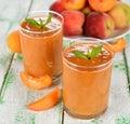 Peach smoothies on a white table Stock Photos