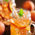 Peach tea close up jar of with striped straw Royalty Free Stock Images