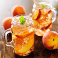Peach tea jar of with striped straw Royalty Free Stock Photos