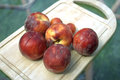 Peach washed on a wooden tray outdoor close shot Royalty Free Stock Photography
