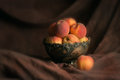 Peaches bowl in an old cooper with one peach just on rhe side shot in studio on a brown backdrop Royalty Free Stock Photo