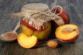 Peaches and pot of jam on a wooden table Royalty Free Stock Photo