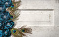 Peacock feathers and flowers on vintage door Stock Photo