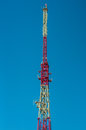 Peak of a telecommunications tower against the blue sky Royalty Free Stock Photo