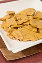 Peanut brittle candy all broken up little pieces easier eating served double plates Stock Photography