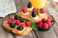 Peanut butter sandwiches topped with fresh berries on healthy wholewheat bread raspberries blackberries and leafy green herbs Royalty Free Stock Image