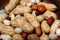 Peanuts in wooden dish with candy closeup macro Royalty Free Stock Photo