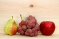 Pear grape and apple on wooden shelf Royalty Free Stock Photography