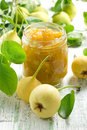 Pear jam in a glass jar and fresh fruits with leav Stock Photos