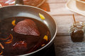 Pear with liquid on pan dark and orange skin sweet sauce for meat red wine and fresh fruit Stock Images