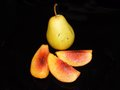 Pear and pieces of peach on black background Stock Images