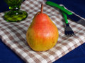 Pear on table cloth big yellow and red beige blue background with green elements Royalty Free Stock Images