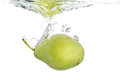 Pear in water sinking into on white Stock Images