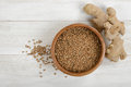 Pearl barley in a pot and ginger on wooden surface. Top view Royalty Free Stock Photo