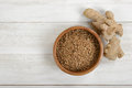 Pearl barley in a pot and whole ginger on wooden surface with copy space Royalty Free Stock Photo