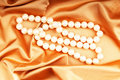 Pearl necklace on the bright satin Stock Image