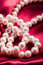 Pearl necklace on red satin background Stock Image