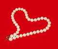 Pearl necklace in the shape of heart on red background Stock Image