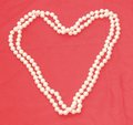 Pearl necklace in the shape of a heart with red background Stock Photography