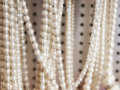 Pearl necklaces for sale fake hanging in shop Stock Photos