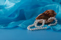 Pearl and Shell, Paua shell and pearl ornaments on blue drapery Royalty Free Stock Photo