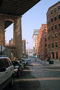 Pearl street dumbo brooklyn nyc cobblestoned down under the manhattan bridge overpass empire state building is seen distant across Royalty Free Stock Photo