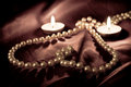 Pearls and candles Stock Images