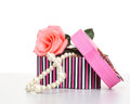 Pearls inside open gift box with pink rose Stock Photo