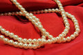 Pearls on red fabric Stock Photo
