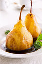 Pears poached in amaretto with chocolate sauce as closeup on a white plate Royalty Free Stock Images