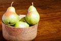 Pears in wood bowl in window light green a on table Royalty Free Stock Photos