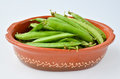 Peas in a pod oval rustic clay pot over white background Stock Image