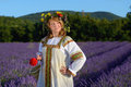 Peasant girl in a flowers wreath dressed in a russians gown stands in lavender field Royalty Free Stock Photo