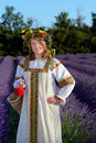 Peasant girl in a flowers wreath dressed in a russians gown stands in lavender field Stock Images