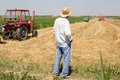 Peasant standing in the field old man on with combine and tractor background Royalty Free Stock Photo