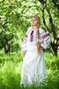 Peasant woman beautiful young girl with a long braid is in the summer garden russian stands in a garden in beautiful clothes Royalty Free Stock Images