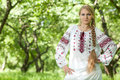 Peasant woman beautiful young girl with a long braid is in the summer garden russian stands in a garden in beautiful clothes Stock Image