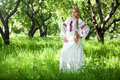 Peasant woman beautiful young girl with a long braid is in the summer garden russian stands in a garden in beautiful clothes Royalty Free Stock Photos