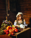 Peasant woman holding a rabbit table with vegetables and fruit stands next to a Royalty Free Stock Photos
